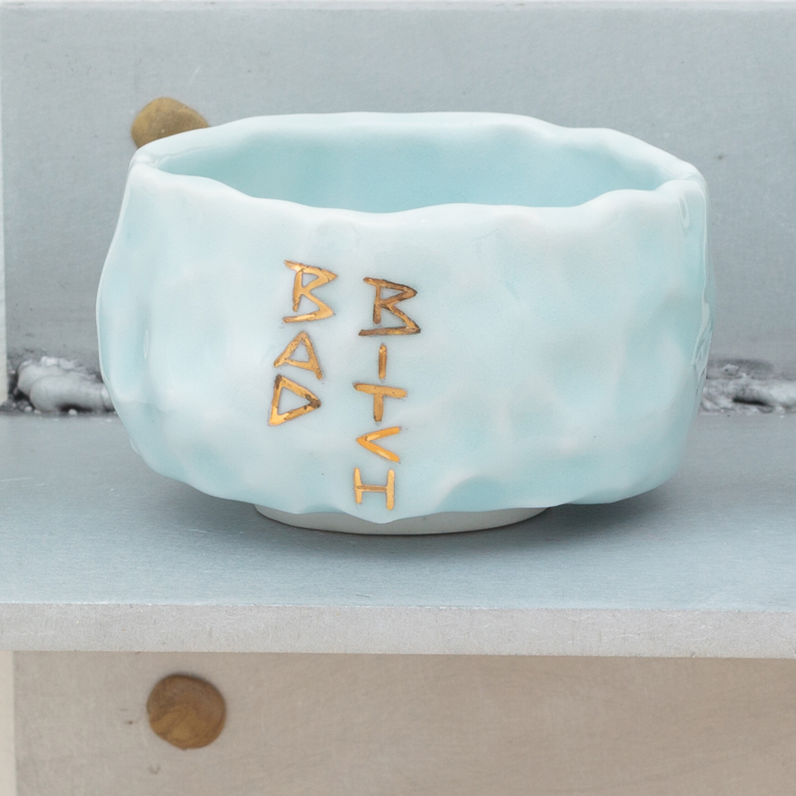 "<p><span class=""name"">Patrice Renee Washington</span><br><em>Bad Bitch Cup (3)</em><span class='media'>Glazed porcelain, gold luster, aluminum, Sculpey clay</span>2.1625 x 2.75 x 2.75in<br>2016<br><a class='inquire' href='mailto:info@gildargallery.com?subject=Artwork Inquiry PWAS0004&body=I am interested in finding out more about Bad Bitch Cup (3) by Patrice Renee Washington'>Inquire</a></p>"